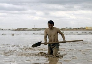 Afghan man searches for his belongings after a flood at Jawzjan